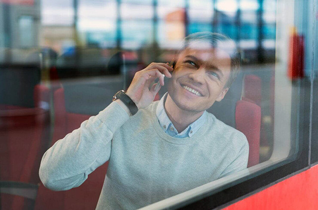 Mann sitzt am Busfenster und telefoniert